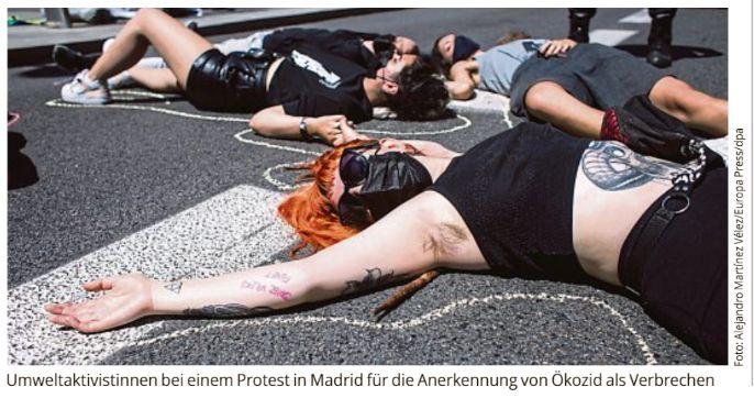 4 Umweltaktivistinnen ausgestreckt liegend am Boden in Madrid für die Anerkennung von Ökozid als Verbrechen